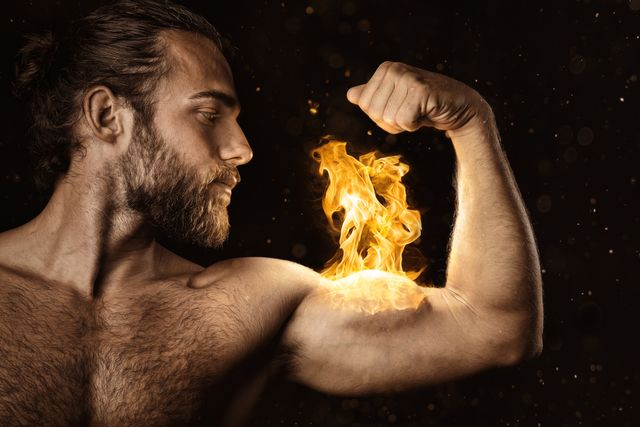 digital composite image of man with fire on biceps against black background