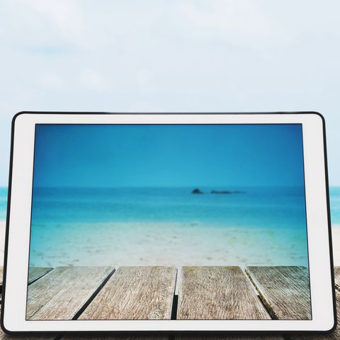 digital tablet with sunglasses on wooden desk at tropical beach