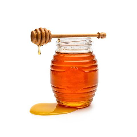 dipper over honey bottle against white background