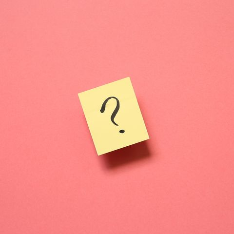 directly above shot of adhesive note with question mark against pink background