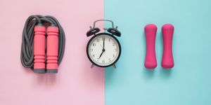 Directly Above Shot Of Alarm Clock With Jump Rope And Dumbbells On Colored Background