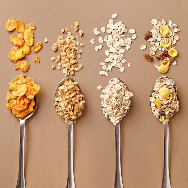 directly above shot of breakfast cereals on spoons over brown background