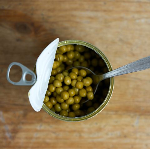 directly above shot of canned peas with spoon on table