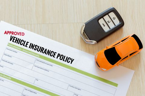Directly Above Shot Of Car Insurance Claim Form With Toy And Key On Table