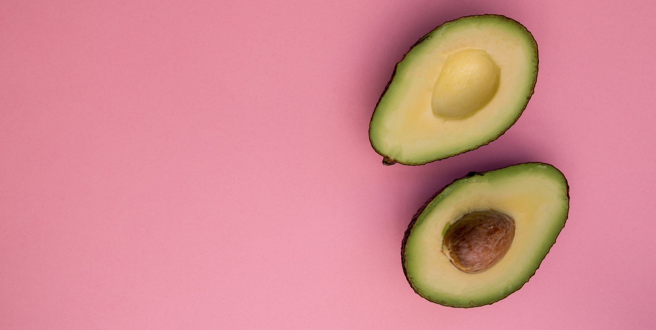 Directly Above Shot Of Halved Avocados Over Pink Background
