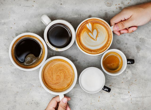 directly above shot of hands holding coffee cups on table