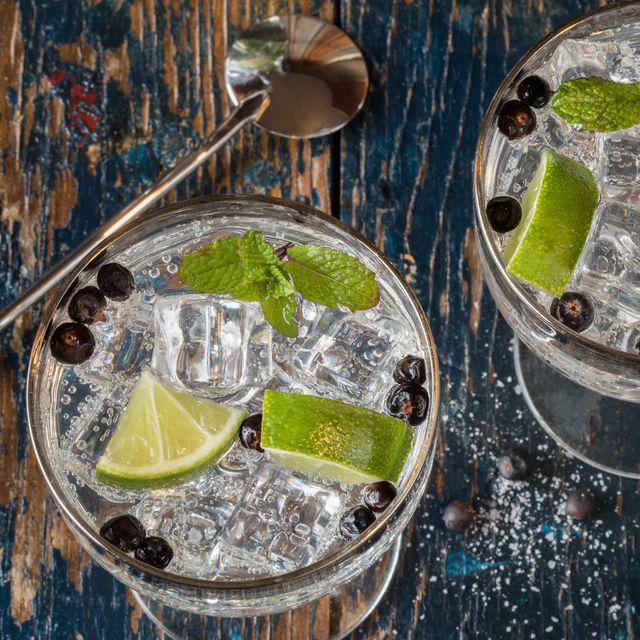 directly above shot of juniper berries and lemon slices in gin tonic glasses on table