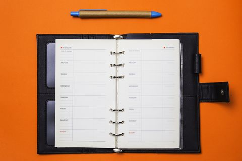 Directly Above Shot Of Open Diary And Book Over Orange Background