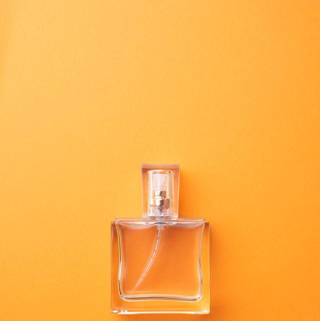 Directly Above Shot Of Perfume Sprayer Against Orange Background