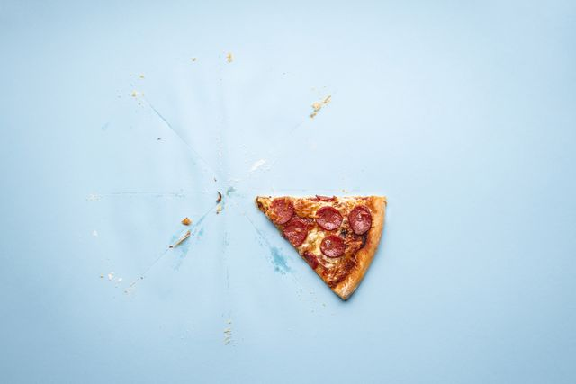 directly above shot of pizza slice on blue background