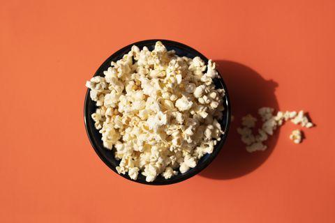 directly above shot of popcorn bowl on the orange background