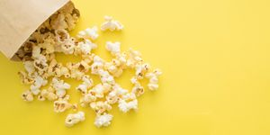 Directly Above Shot Of Popcorn Spilling Out From Paper Bag Over Yellow Background