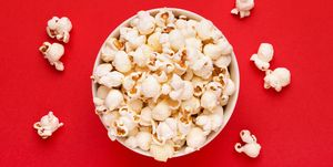 Directly Above Shot Of Popcorns In Bowl Against Red Background