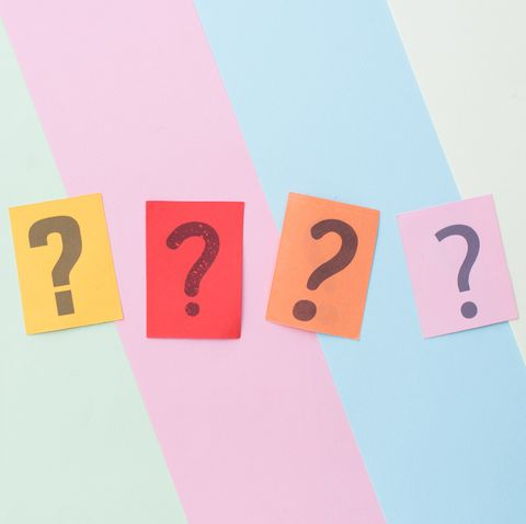 directly above shot of question marks on colorful papers on table