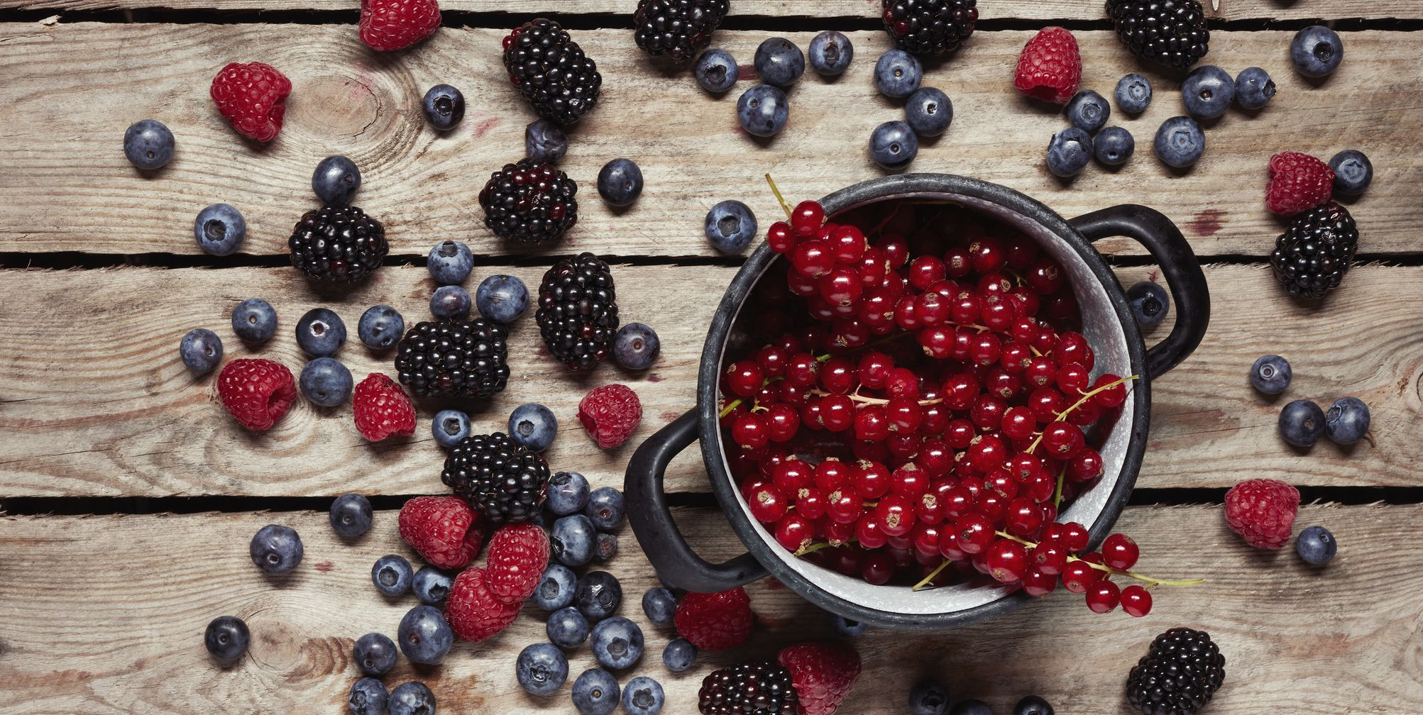 Directly above shot of red currants in container surrounded with berry fruits on table