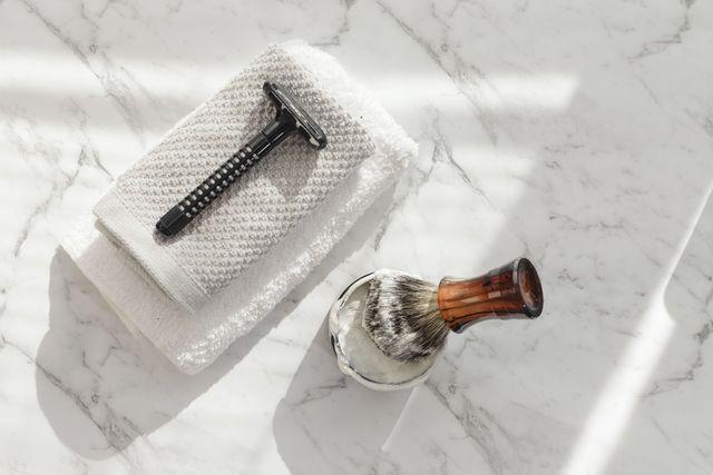 directly above shot of shaving brush and razor on marble floor