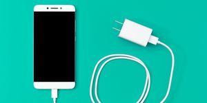Directly Above Shot Of Smart Phone And Charger Turquoise Background
