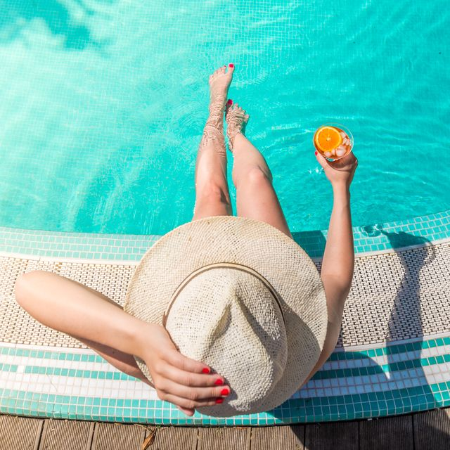 directly above shot of woman with drink sitting at poolside