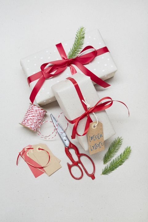"directly above shot of wrapping christmas gifts with ""for you"" gift tag and red scissors on gray background"
