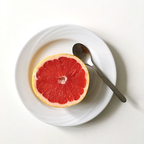 Directly Above View Of Grapefruit In Plate On White Background