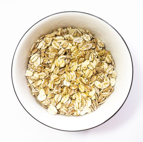 directly above view of oats flakes in bowl on white background