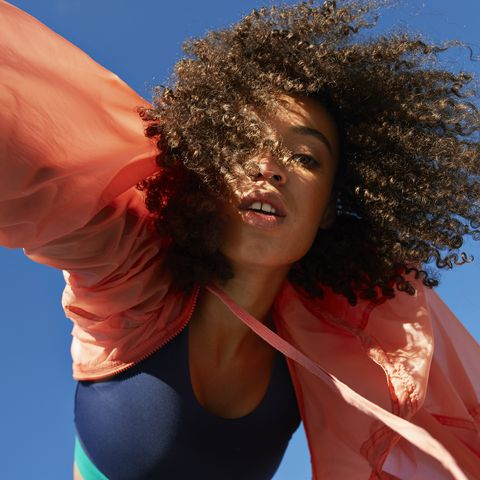directly below shot of female athlete with curly hair against clear sky
