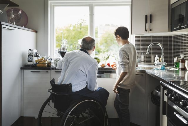 disabled father preparing food son in kitchen