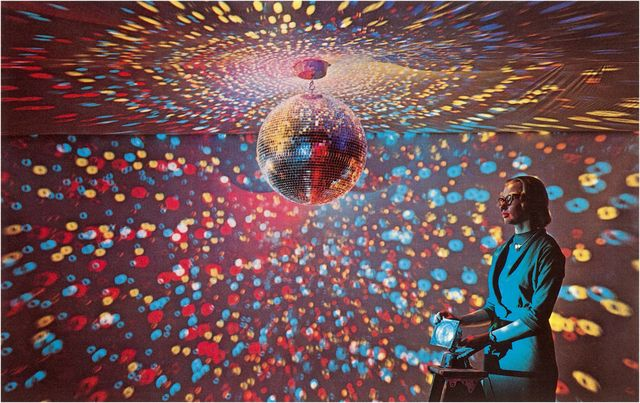 vintage color photograph of a young woman in glasses and a blue suit manipulating an apparatus that produces a colorful bubble light display covering dark walls and ceiling beneath a large shimmering disco ball, 1960s photo by found image holdingscorbis via getty images