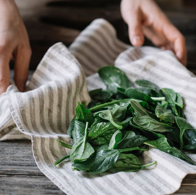 hands with dish towel and spinach