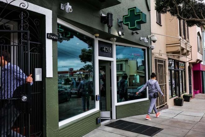 People walk by the exterior of cannabis dispensary The Green Cross in San Francisco.