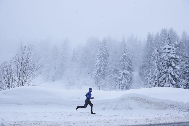 distant view of male runner running in deep snow, gstaad, switzerland