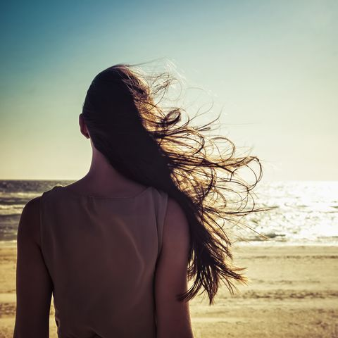 hair of caucasian woman blowing in wind at beach