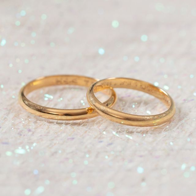 Two golden wedding rings on white shiny background