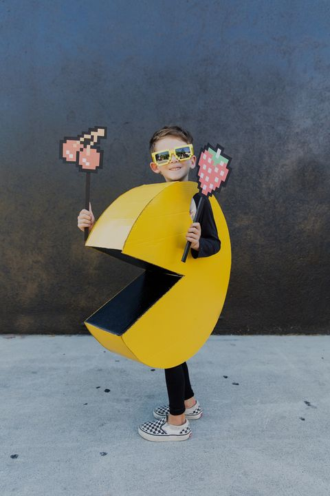 kid dressed as pac man holding fruits