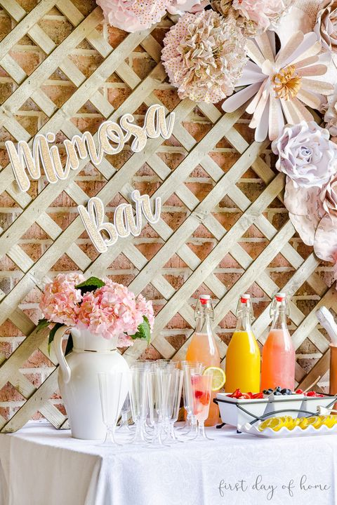 table with white cloth, pink flowers, juices, clear glasses, and fruit