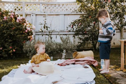 two toddlers on picnic blanket in garden