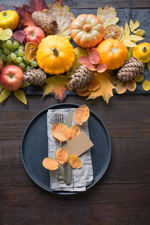 fall table place setting with orange dry leaves and pumpkins vertical format centerpieces thanksgiving day view from above