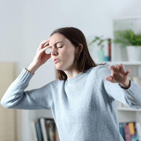 dizzy woman suffering vertigo attack at home