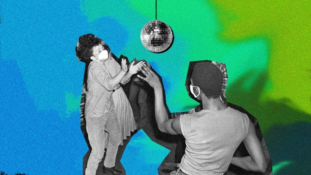 two women dacing beneath a disco ball with masks on