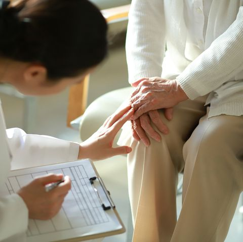doctor checking patient's knee pain