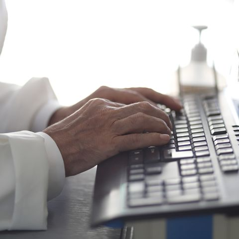 doctor reviewing records on desktop pc