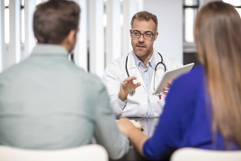 doctor talking to couple in medical practice