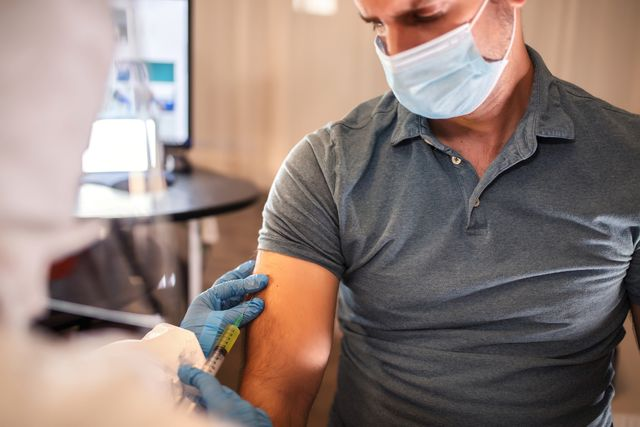 doctor wearing protective workwear injecting vaccine into patient's arm
