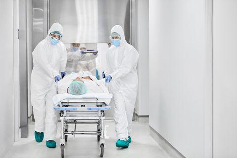 doctors pushing patient on gurney in corridor