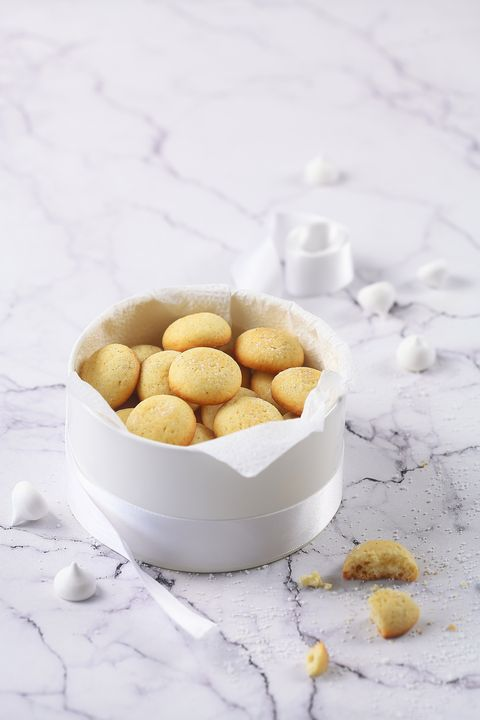 little round vanilla butter cookies, round box, plate, coffee, light marble background