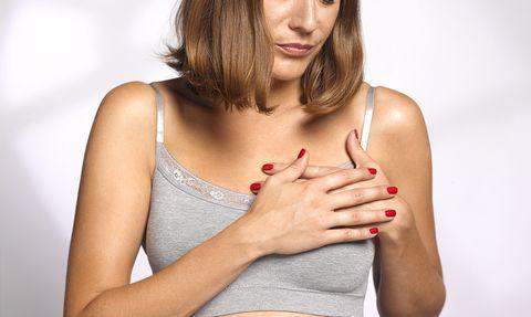 Mujer con dolor en el pecho por la menstruación