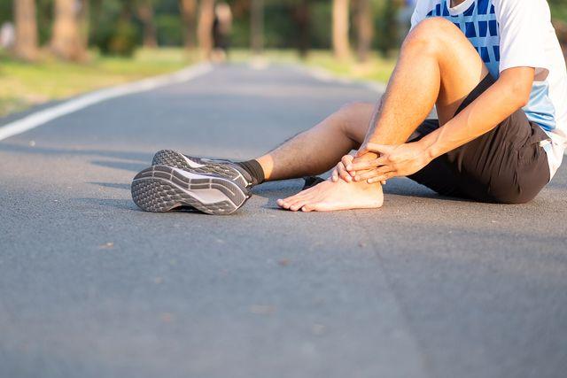 un corredor sentado en la carretera y con el pie descalzo se duele del empeine o parte superior del pie