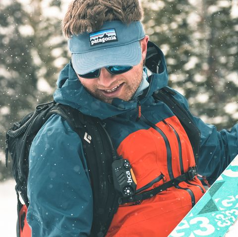man wearing winter gear holding ski
