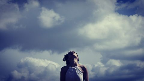 Low Angle View Of Mid Adult Woman Standing Against Cloudy Sky