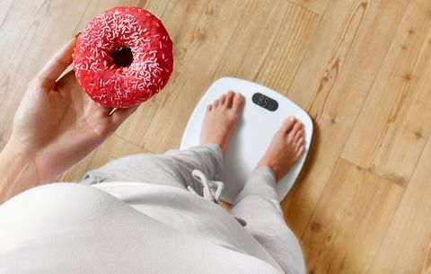 Standing on the bathroom scale with a donut